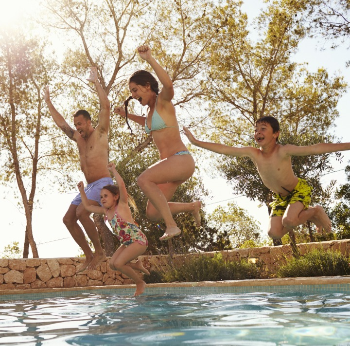 Family jumping in the swimming pool